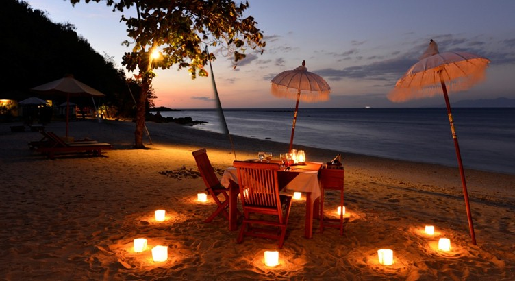 Comida de la luz de la vela en la playa
